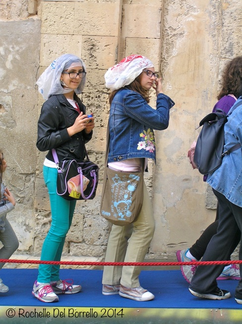 Clever girls not getting wet in line at the Infiorata, Noto 2014.